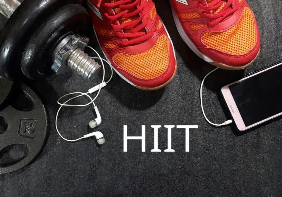 Dumbbell, smartphone and sport shoes on gym floor with word HIIT
