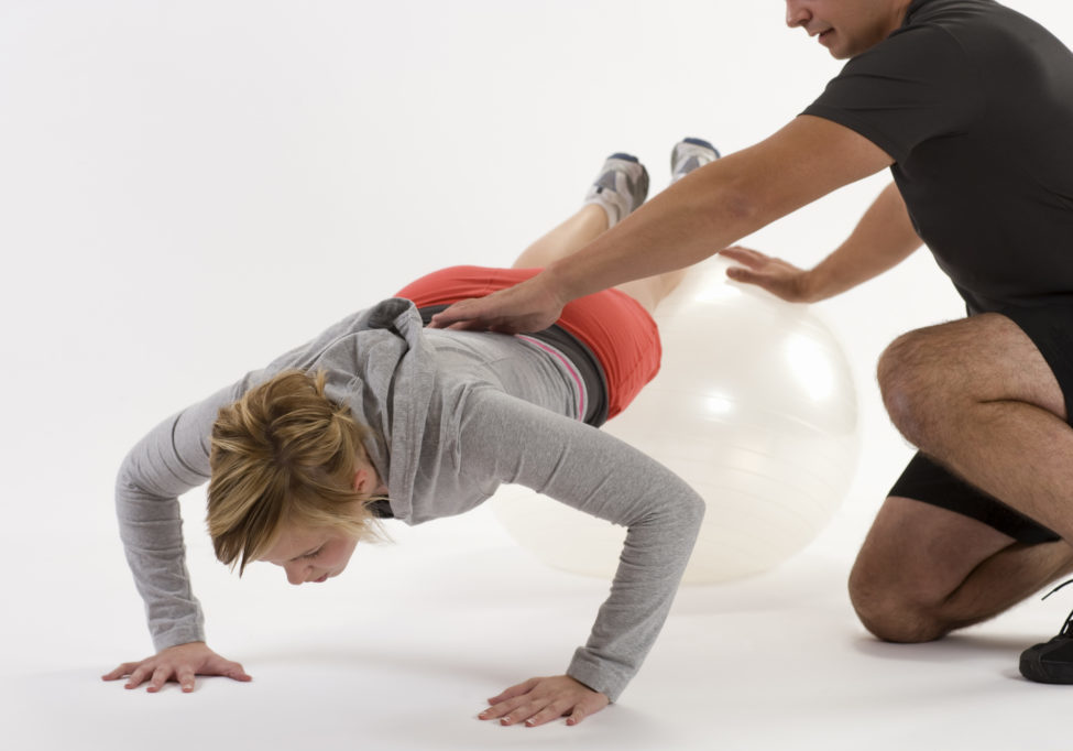 Female client working out on balance ball with fitness trainer